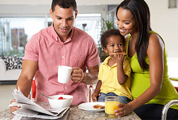 Tageseltern mit Kind beim Frühstücken