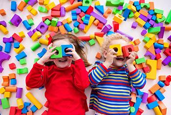 Zwei Kinder liegen mit Spielzeug am Boden