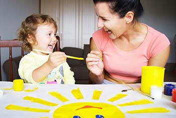 Tagesmutter mit Tageskind beim Malen
