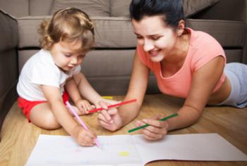 Tagesmutter liegt mit Kind am Boden und zeichnet