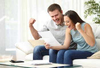 Paar hält Zettel in der Hand und freut sich